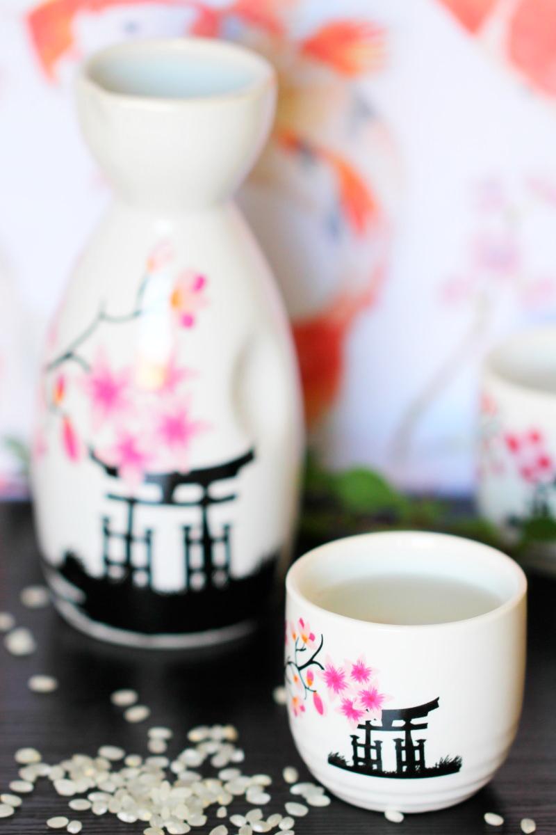 Zu sehen ist ein Sake Set mit Blütendekor und einem japanischen Schreintor als Verzierung auf dem Porzelan.